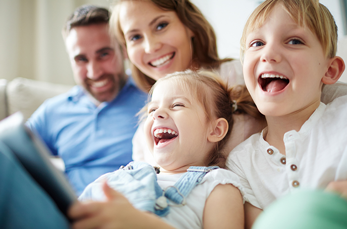 A family sitting together with kids and laughing