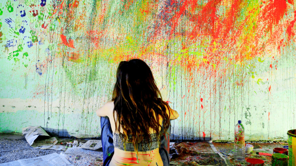 Woman Sitting On Floor Against Messy Wall