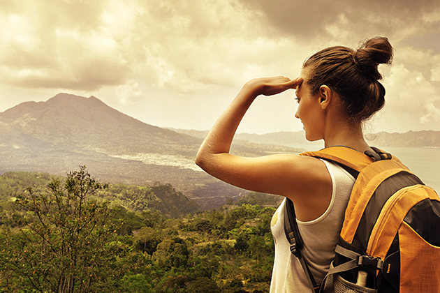 A woman standing on a mountain and wearing a bag